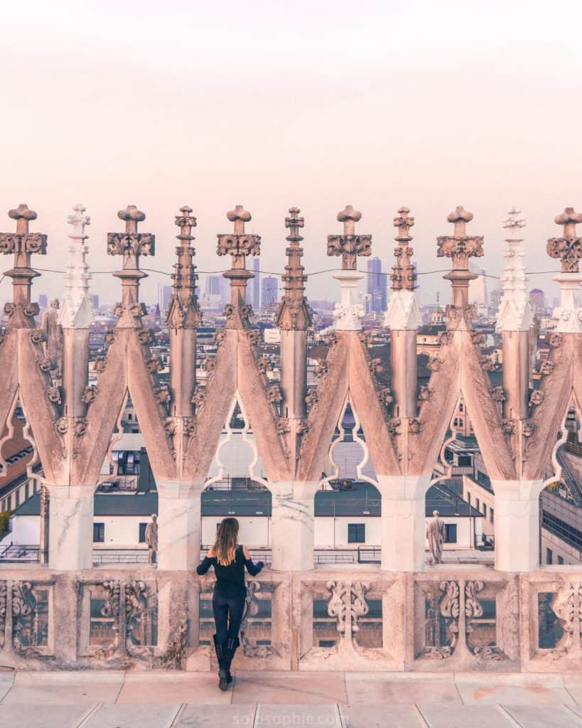 Girl on the Duomo di Milano rooftop terrace overlooking the city of Milan, Northern Italy at sunset