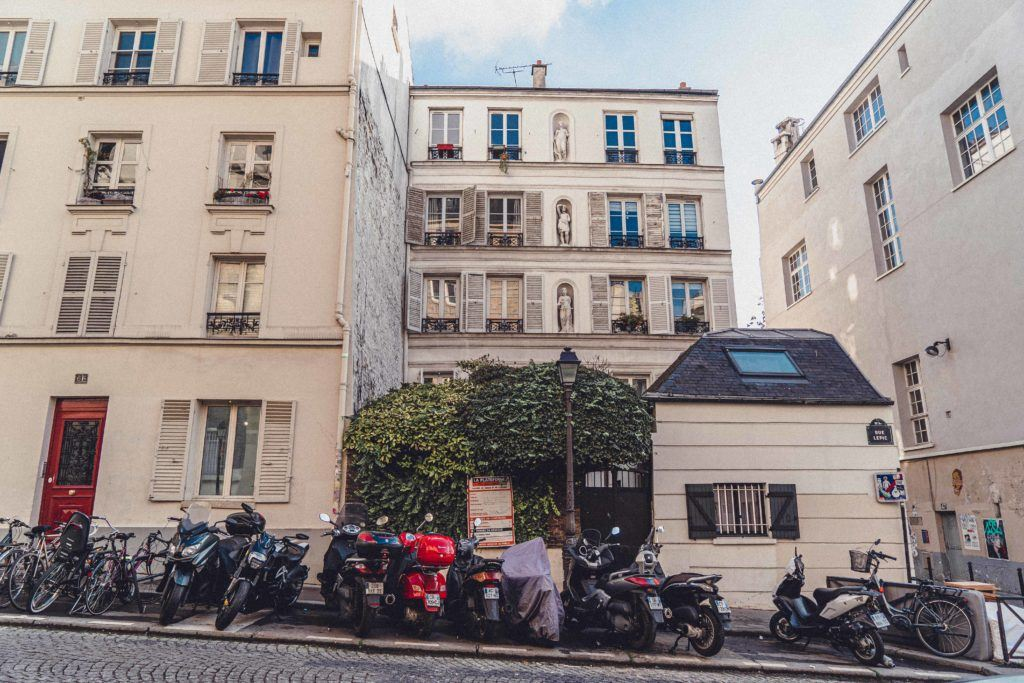 historic buildings with scooters in front on rue Lepic in Paris, France